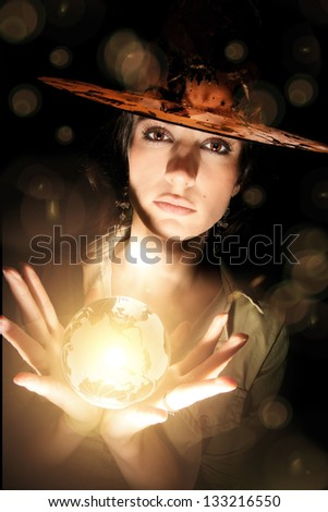 Girl with witch hat and crystal lighting ball. Halloween concept.