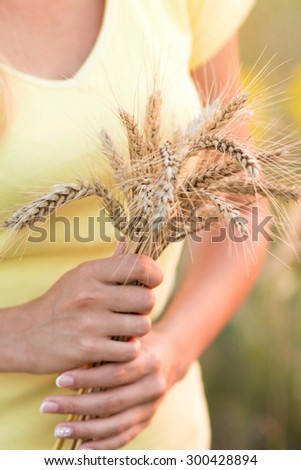 Girl with with ripe ears of barley in hand