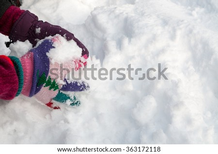 Girl with woolen knitted gloves making snowball - stock photo