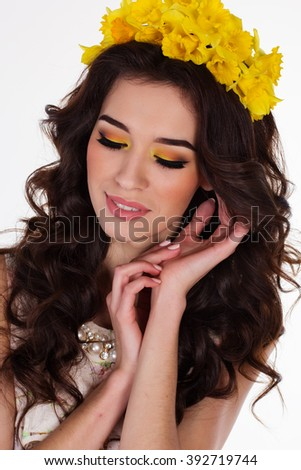 Girl with wreath of daffodil flowers and fashion makeup