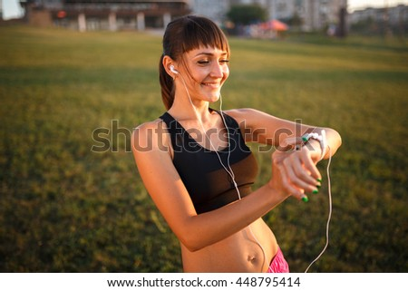 girl with wrist fitness bracelet outdoors. smiling on her face