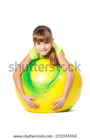 girl with yellow ball doing exercises on a white background - stock photo