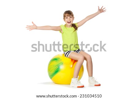 girl with yellow ball doing exercises on a white background