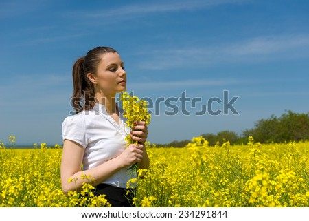 girl with yellow flowers on the field - stock photo