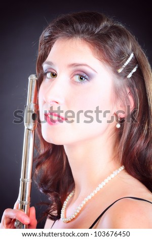 girl woman plays the flute on a black background