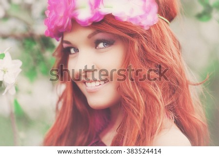 girl woman red-haired in flowering spring garden