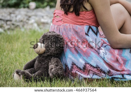 Girl (women) with her Teddy bear in the park back to back