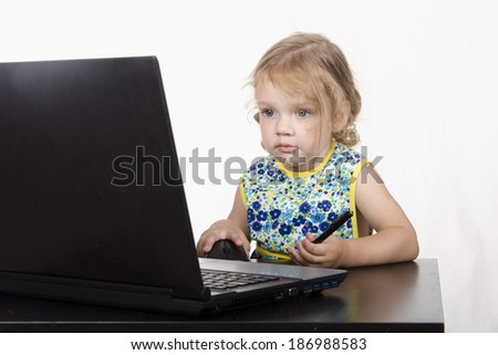 girl working at a laptop. Laptop stands on table. girl looked mysteriously in frame
