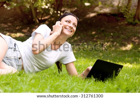 girl working freelance. makes chat in the park