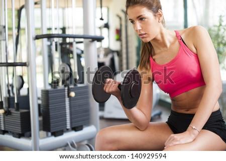 Girl working hard at gym - stock photo