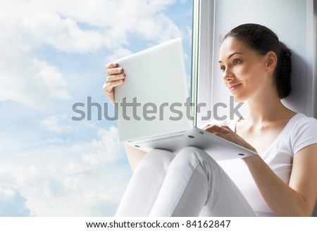 Girl working on computer in light room - stock photo