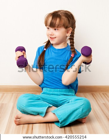 girl working out with dumbbells on the floor at home - stock photo