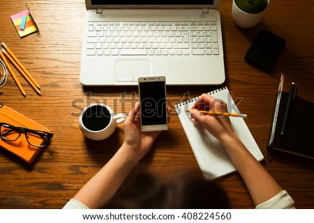 Girl works remotely at her computer. She had been using laptop, smartphone, notebooks, pencils, pen, stickers and headphones. - stock photo