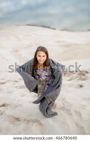 girl wrapped in a blanket on the sand runs