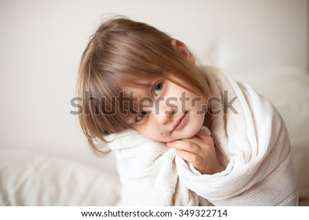 girl wrapped in a light white  blanket, warm and cozy, cold, winter light background - stock photo