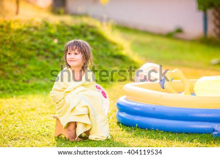 Girl wrapped in towel sitting by the swimming pool - stock photo