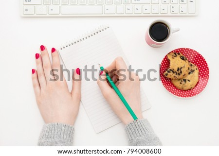 girl writes in a notebook, standing next to a Cup of coffee, cookies, top view, background with copy space, for advertising