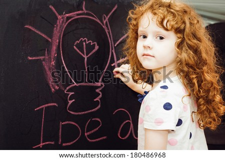 Girl writes in chalk on a blackboard. Education concept. - stock photo