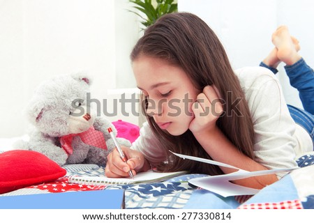 Girl writes lying on the bed - stock photo