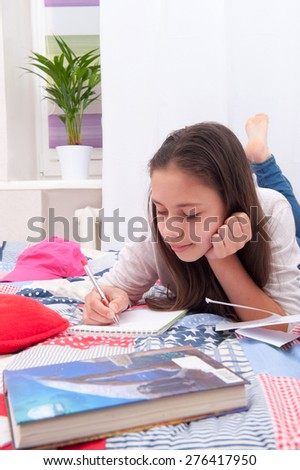 Girl writing in a notebook lying on the bed - stock photo