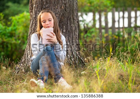 Girl writing in a notebook while sitting in the park - stock photo