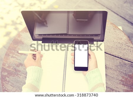 girl writing in a notebook with a cell phone and a laptop, vintage color effect - stock photo
