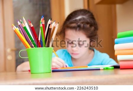 Girl writing on desk - stock photo