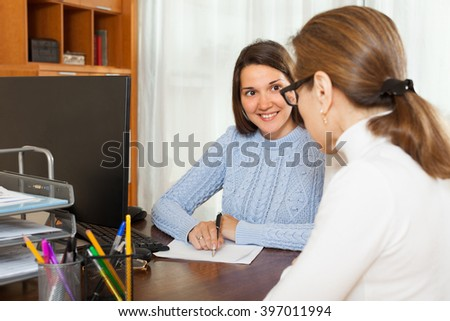 Girl written questionnaire for employee of the company at table in office - stock photo