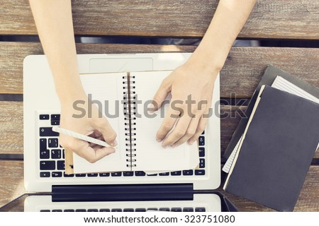 Girl wrote in a diary with books and laptop - stock photo