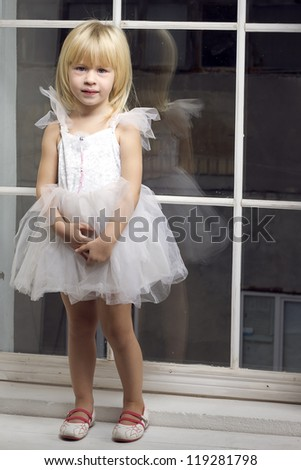 Girl 3 years old in a beautiful white dress near the winter window