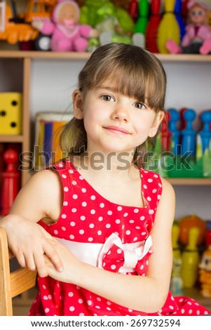 Girl 6 years with blond hair in a red dress with white polka dots sitting on a chair - stock photo