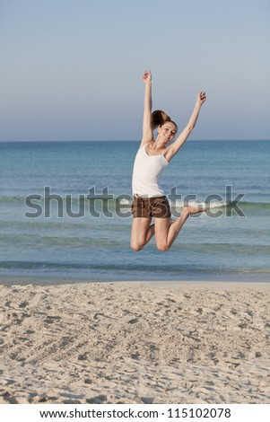 Girl young cheerful woman jumping in the air on the beach in the sand in the morning on the sea in summer vacation