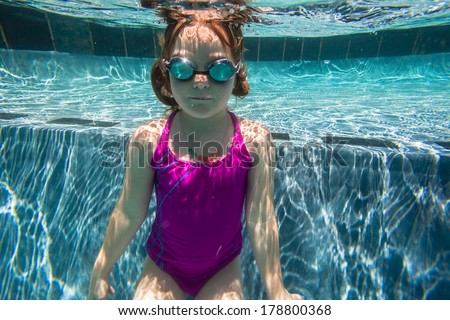 Girl Young Underwater Goggles Young girl swimming underwater with goggles. - stock photo