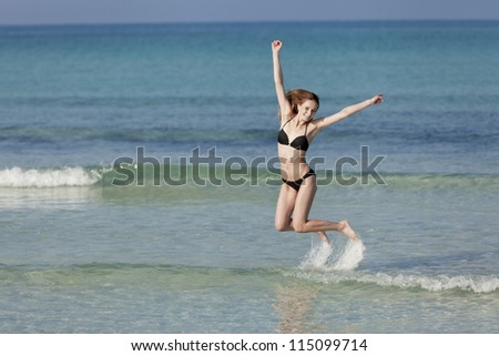 Girl, young woman jumping in the water at the beach jumping happily in the sea in summer vacation