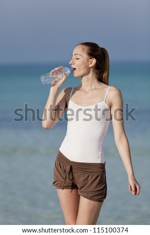 Girl young woman refreshing drinks water from a bottle on the beach by the sea in summer vacation