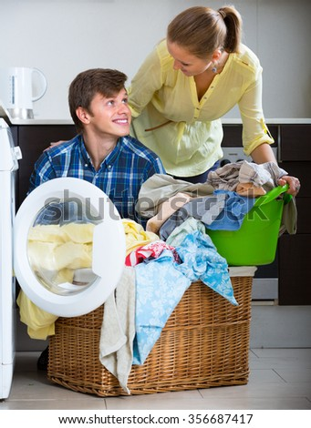 girlfriend and boyfriend doing regular laundry and smiling at home