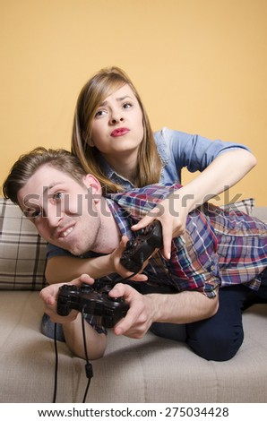 Girlfriend and Boyfriend playing video games funny  - stock photo