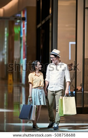 Girlfriend and boyfriend with shopping bags looking at each other