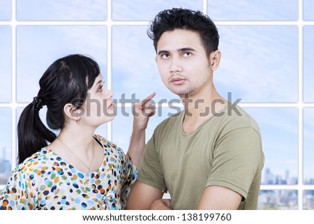 Girlfriend angry at boyfriend in apartment with cityscape - stock photo