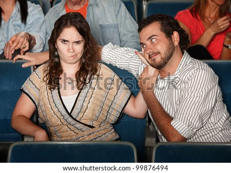 Girlfriend annoyed with rude man in theater - stock photo