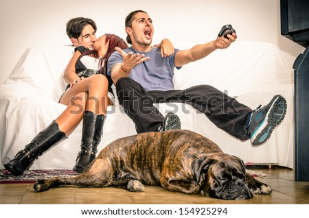Girlfriend cheating Boyfriend with Lover behind the Sofa while playing Videogames - stock photo