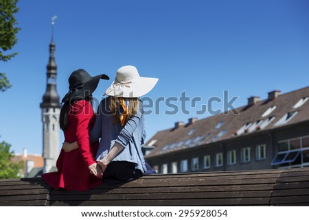 Girlfriend couple holding hands on a bench - stock photo