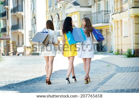 Girlfriend go shopping. Three attractive young girl holding shopping bags while pass near the store. View from the back of girls - stock photo
