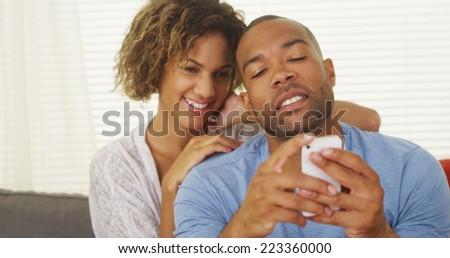 Girlfriend watching over boyfriend's shoulder as he texts - stock photo