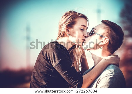 Girlfriend with her boyfriend kising outdoor in the forest - stock photo