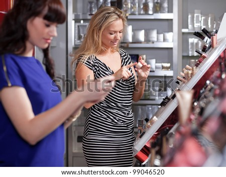 Girlfriends buying and testing cosmetics in a beauty store - stock photo