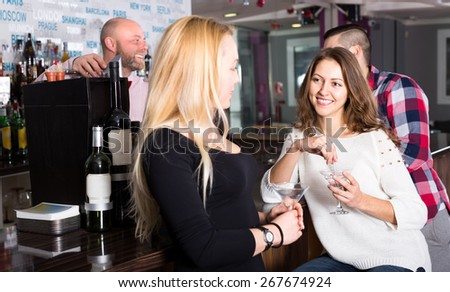 Girlfriends chatting at the bar and drinking cocktails - stock photo