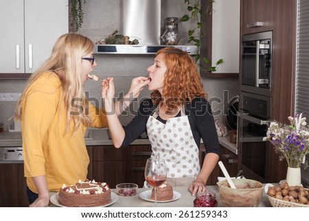 Girlfriends feeding each other with a cake and cooking together in the kitchen at home.
