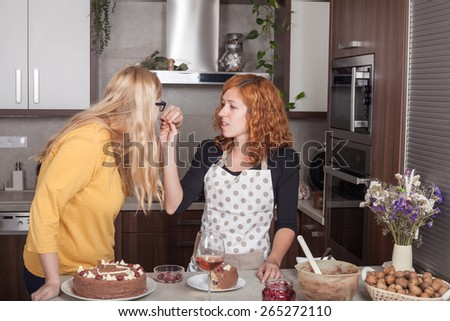 Girlfriends feeding each other with and cooking together in the kitchen at home.
