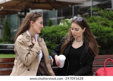 Girlfriends having fun on bench outdoors daytime - stock photo